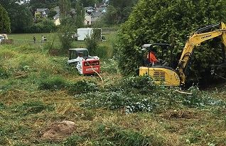 Equipment cleans up brush in a grassy area