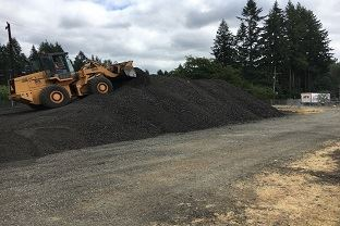 A bulldozer piles up asphalt grindings